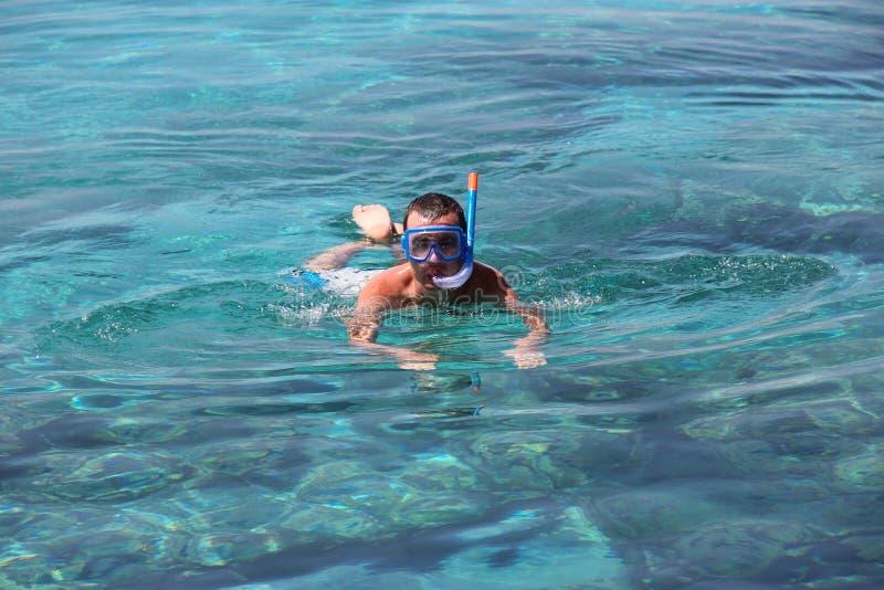 Um homem em uma máscara flutua no mar Mediterrâneo imagem de stock