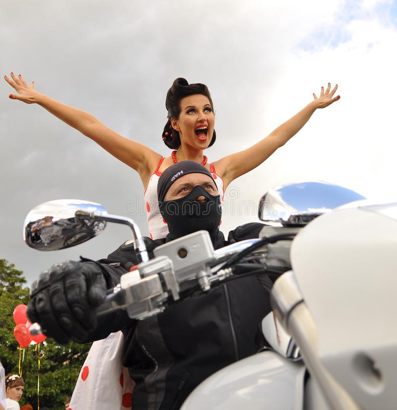 Um homem em uma máscara preta senta-se atrás da roda de uma motocicleta branca atrás dele senta uma menina bonita em um fundo do  fotografia de stock royalty free