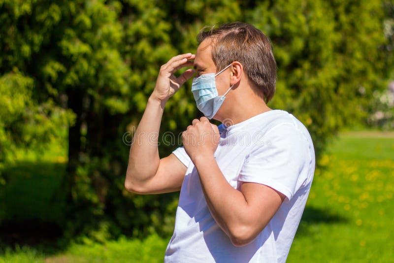 Um homem em uma m?scara da alergia, em um t-shirt branco, suportes no parque imagem de stock royalty free