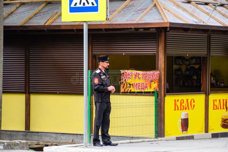 Um homem em um uniforme do cossaco em uma loja do mel fotografia de stock