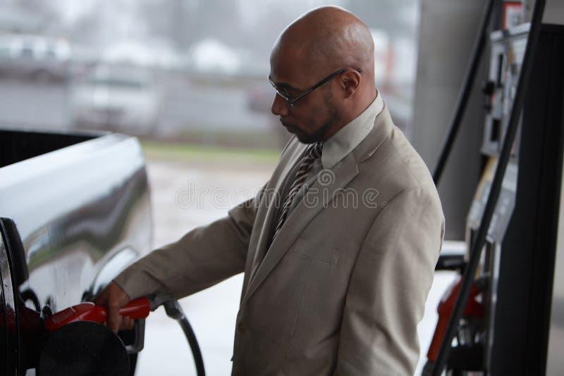 Um homem enche seu depósito de gasolina fotos de stock