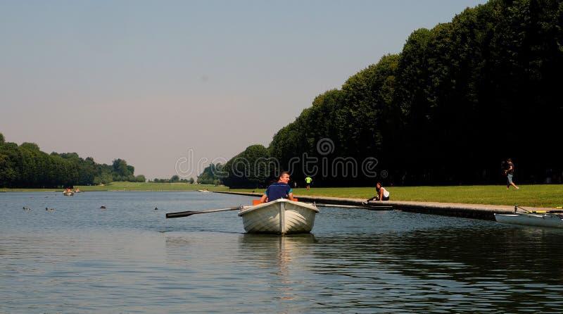 Um homem enfileira um barco de pá em um canal imagem de stock royalty free