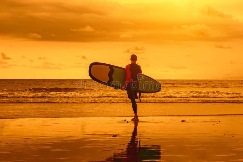 um homem entra na água para surfar fotografia de stock