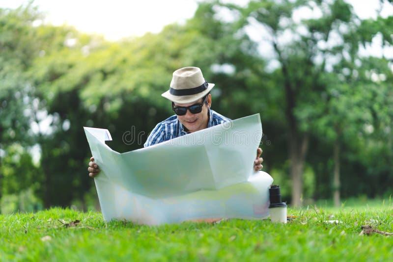 Um homem envelhecido meados de do viajante feliz senta exterior no parque verde, lookin foto de stock royalty free