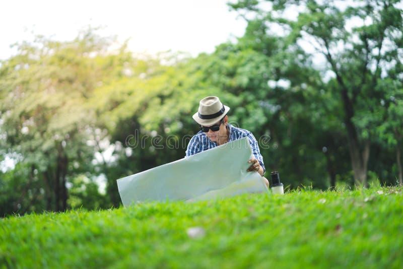 Um homem envelhecido meados de do viajante feliz senta exterior no parque verde, lookin fotografia de stock royalty free