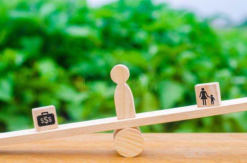 Um homem escolhe entre a família e o trabalho nas escalas O conceito da escolha entre uma carreira e da suspensão para fora com s foto de stock