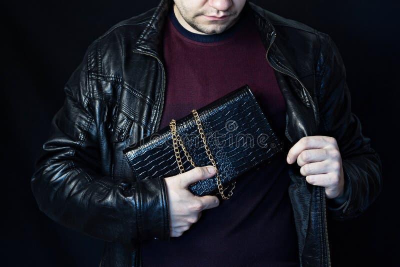 Um homem esconde uma bolsa do ` s da mulher em seu peito, o roubo de uma bolsa, um revestimento preto do fundo imagens de stock