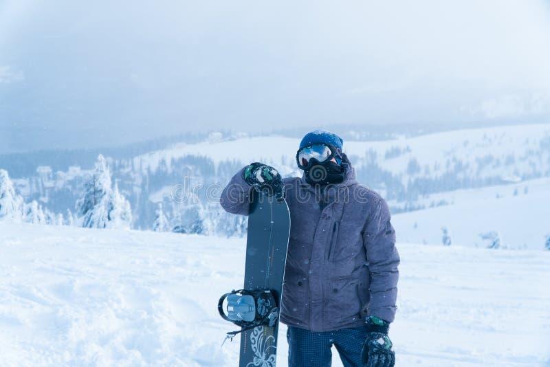 Um homem está com snowboarding montagem do suporte snowboard do homem fotografia de stock royalty free