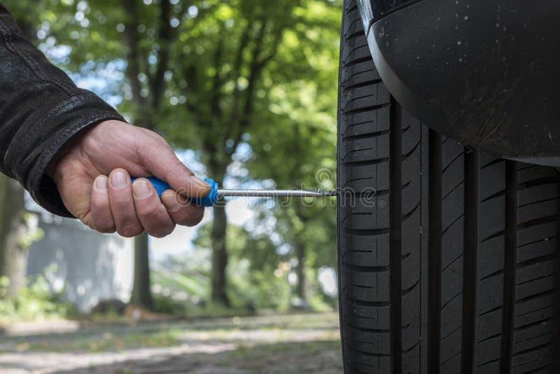Um homem está demulindo um pneu de carro foto de stock