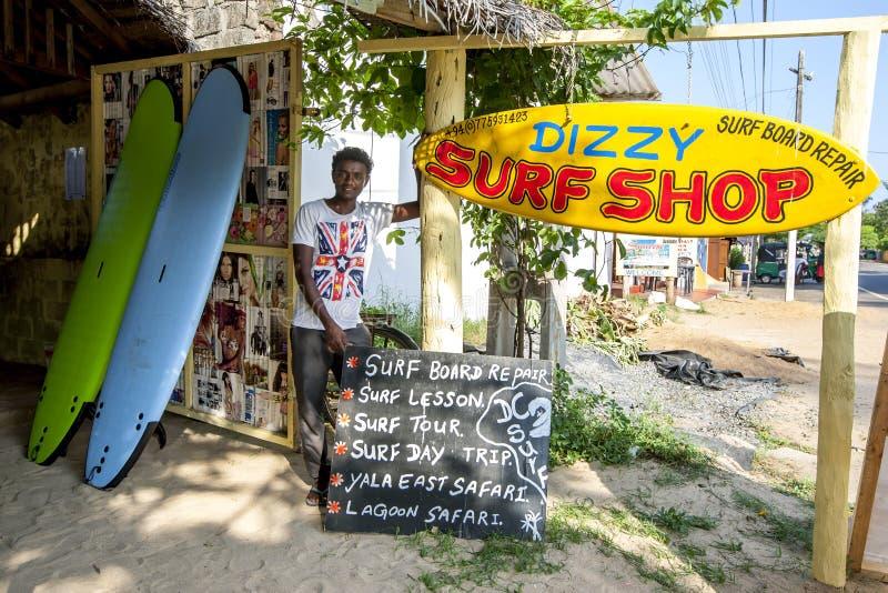 Um homem está em Dizzy Surf Shop imagens de stock