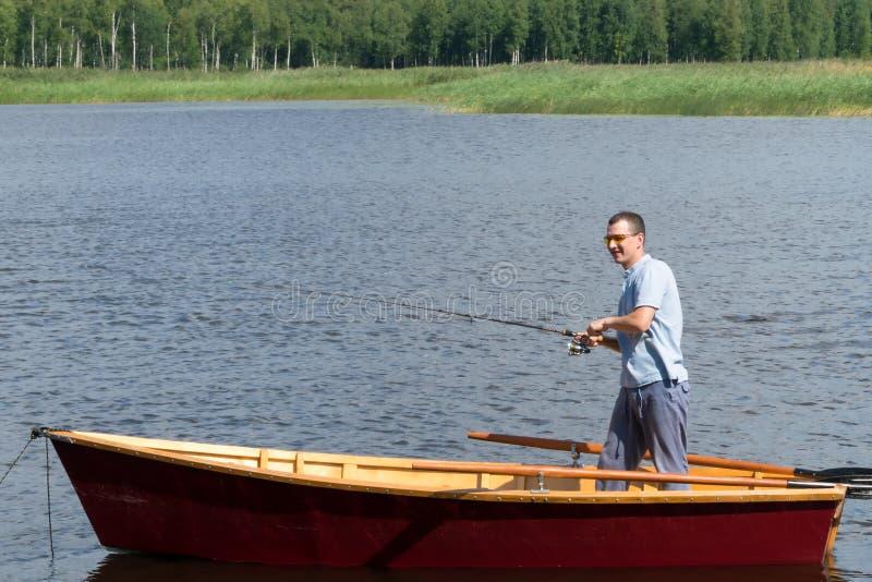 Um homem está estando em um barco de madeira no meio do lago e está girando um carretel de gerencio a fim retirar os peixes trava imagem de stock royalty free