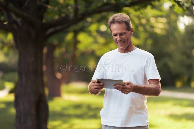 Um homem está estando em um parque com uma tabuleta cinzenta em suas mãos Olha a tela da tabuleta fotografia de stock