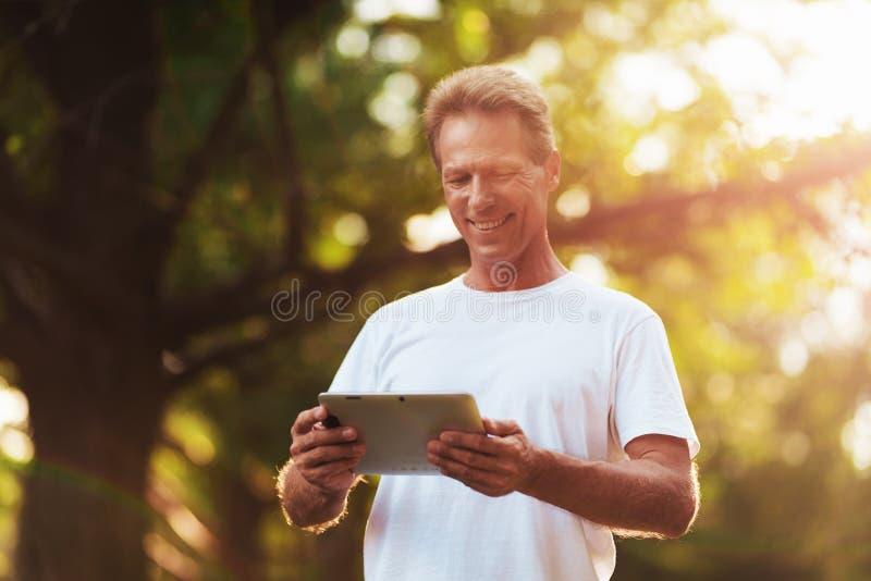 Um homem está estando em um parque com uma tabuleta cinzenta em suas mãos Olha a tela da tabuleta foto de stock royalty free