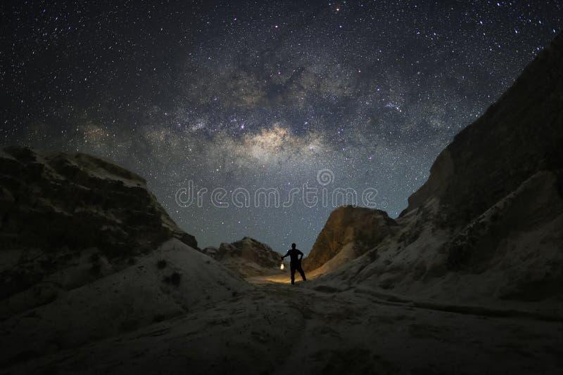 Um homem está estando guarda uma lanterna de querosene do monte ao lado da galáxia da Via Látea fotos de stock royalty free