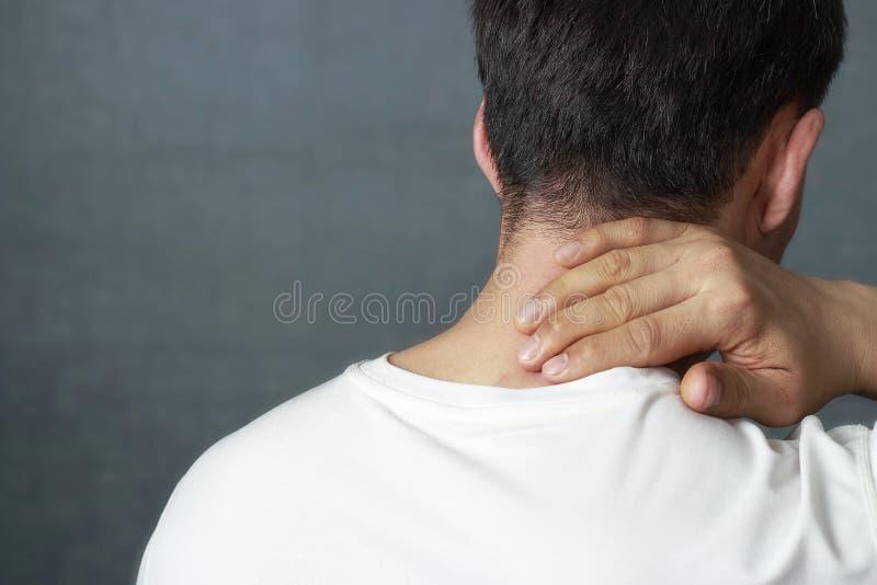 Um homem está fazendo massagens um pescoço dorido, close-up, vista traseira fotografia de stock