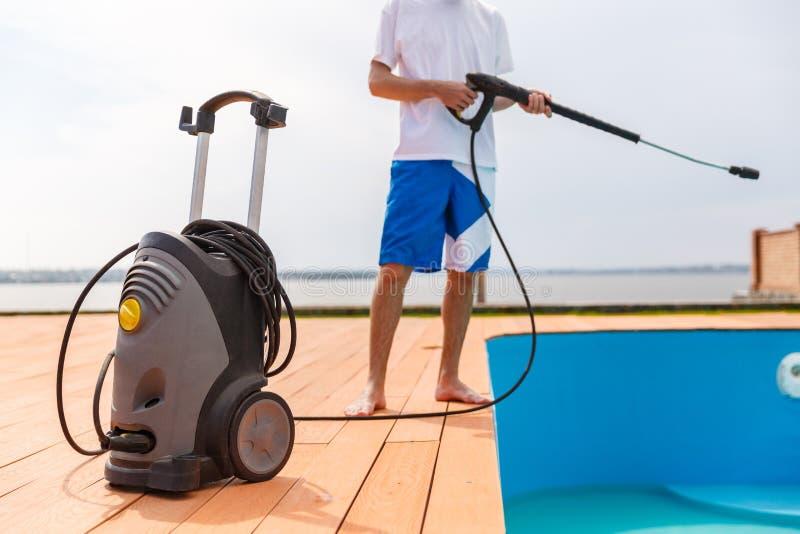 Um homem está limpando uma piscina imagem de stock royalty free