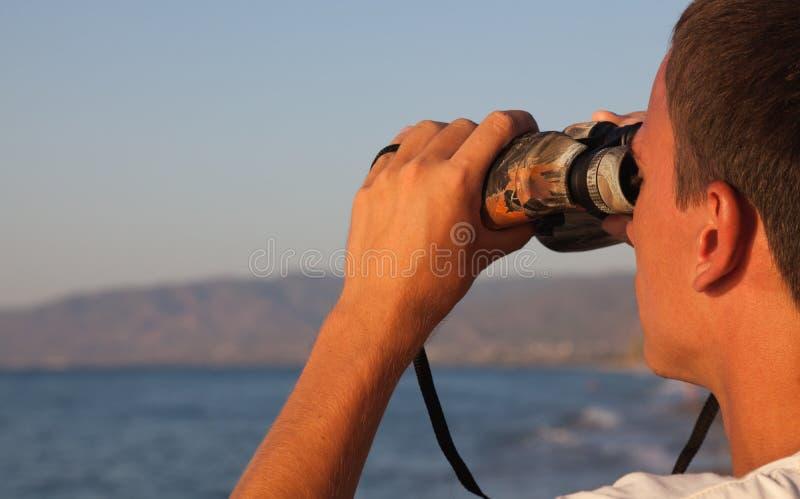 Um homem está olhando ao binocular imagens de stock royalty free