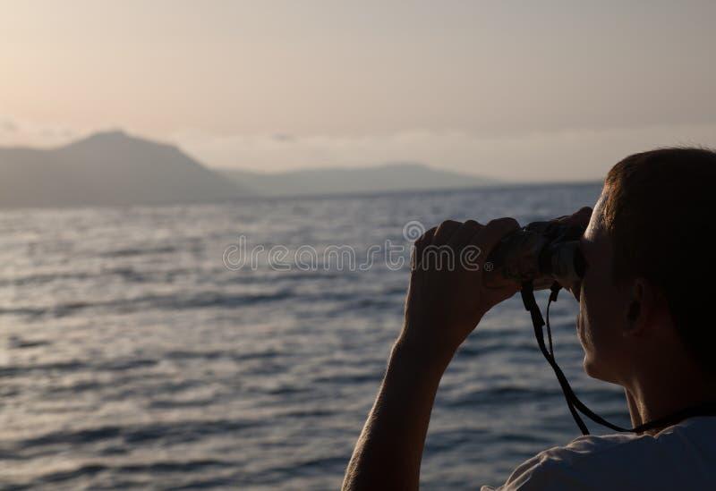 Um homem está olhando ao binocular imagem de stock royalty free