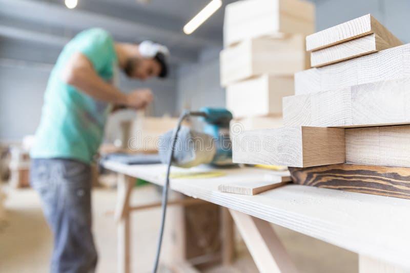 Um homem está processando uma árvore joiner Um carpinteiro Processos do Woodworking imagem de stock royalty free