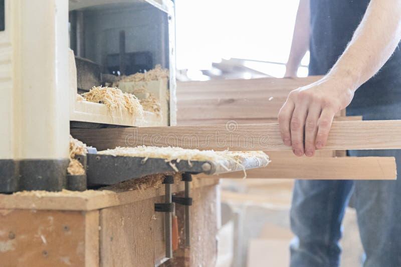 Um homem está processando uma árvore joiner Um carpinteiro Processos do Woodworking imagens de stock royalty free