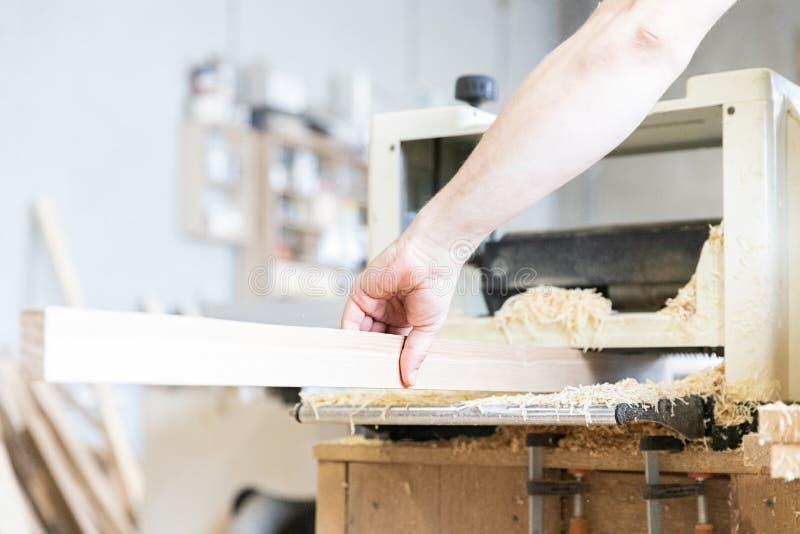 Um homem está processando uma árvore joiner Um carpinteiro Processos do Woodworking fotos de stock