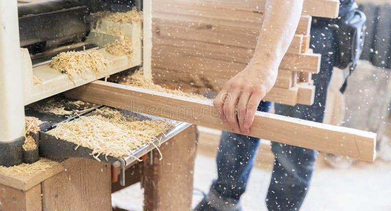 Um homem está processando uma árvore joiner Um carpinteiro Processos do Woodworking foto de stock