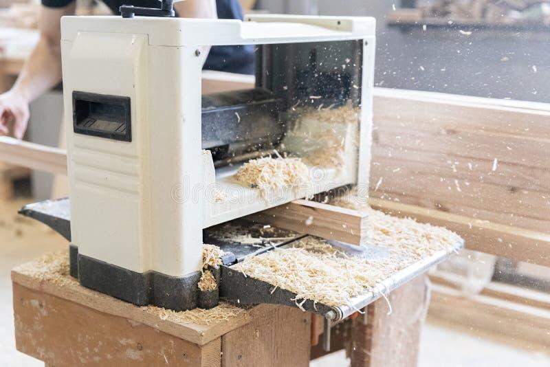 Um homem está processando uma árvore joiner Um carpinteiro Processos do Woodworking fotos de stock royalty free