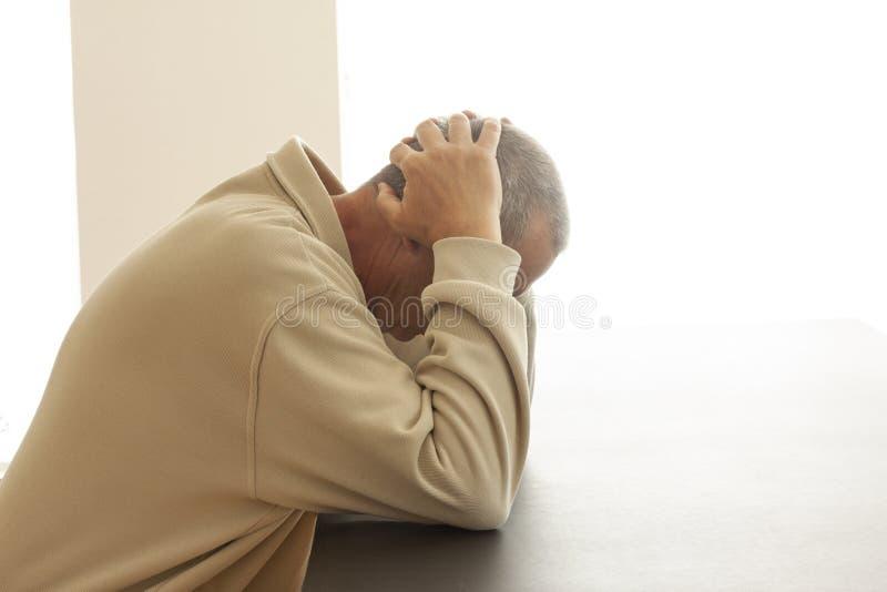 Um homem está sentando-se apenas em uma cabeça da tabela enterrada em suas mãos Um sinal do sofrimento, da tristeza ou do abandon fotografia de stock