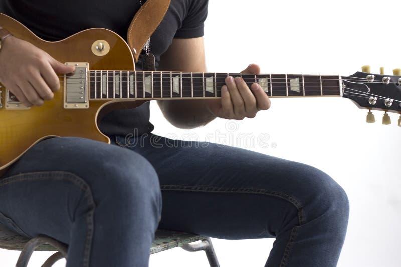 Um homem está sentando-se em uma cadeira e está jogando-se uma guitarra elétrica em um fundo branco fotos de stock royalty free