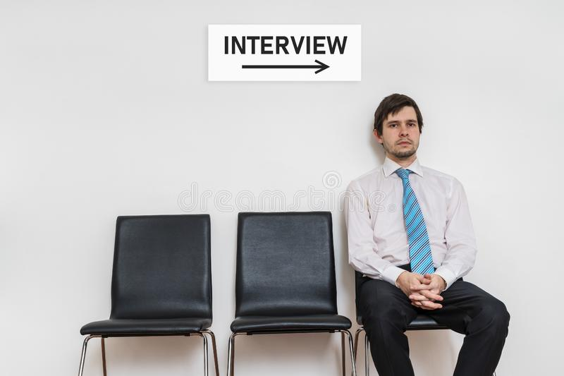 Um homem está sentando-se na cadeira na sala de espera e na entrevista de espera fotos de stock royalty free
