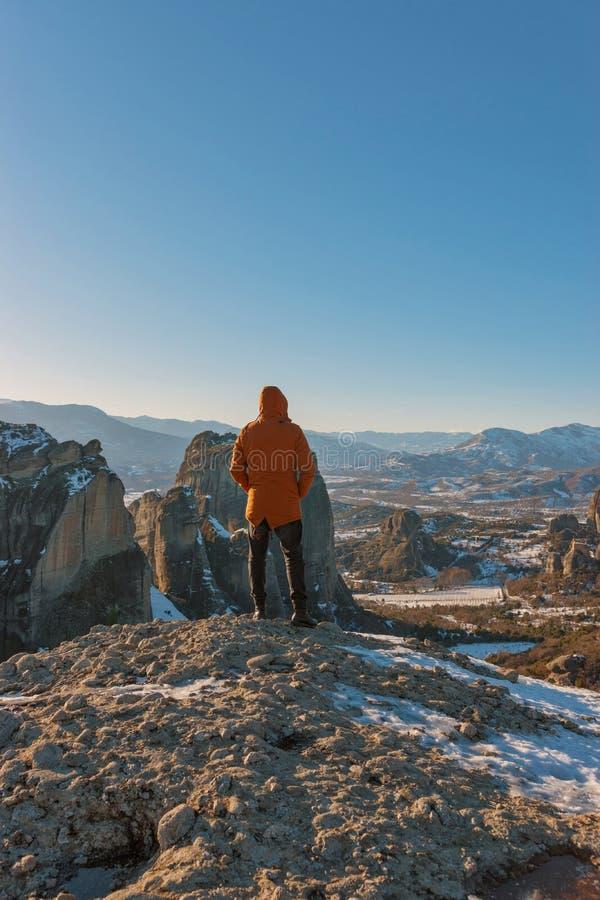 Um homem está sobre montanhas rochosas e aprecia a vista bonita do monastério de Meteora em Grécia foto de stock royalty free