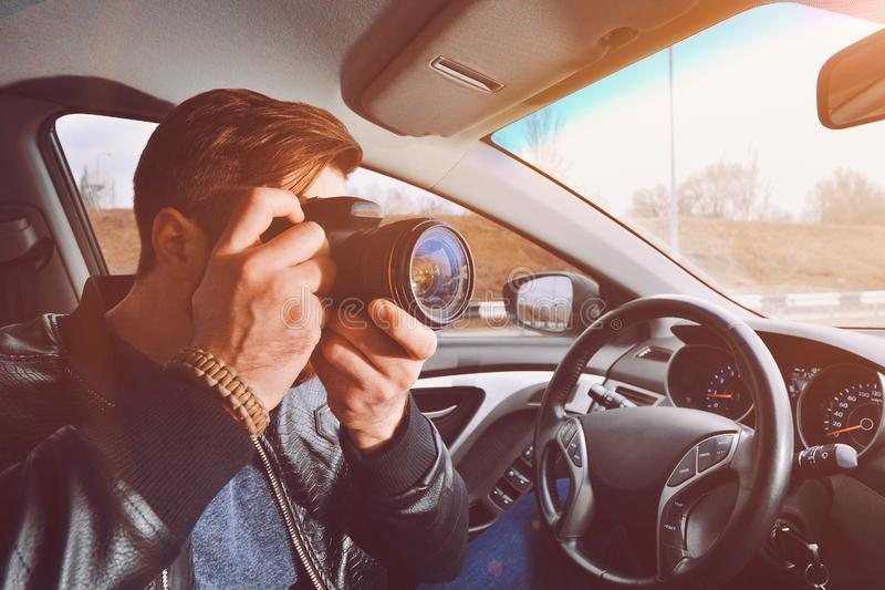 Um homem está tomando imagens de uma janela de carro Viajante do fotógrafo O trabalho de um detetive privado fotografia de stock