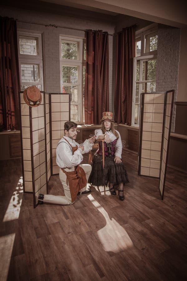 Um homem est? fazendo uma tatuagem para uma mulher, steampunk do vintage imagem de stock royalty free