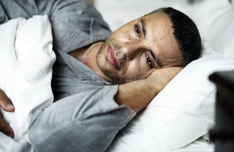 Um homem estabelece na cama foto de stock