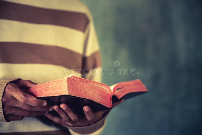 Um homem esteve de leitura a Bíblia ou de leitura um livro em um muro de cimento fotografia de stock