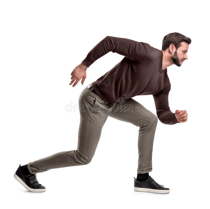Um homem farpado do ajuste na roupa ocasional está em uma baixa posição pronto para ser executado em um fundo branco fotografia de stock royalty free