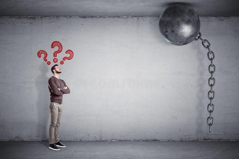 Um homem farpado está com grandes sinais vermelhos da pergunta acima dele e olha uma bola de destruição colada ao teto imagem de stock