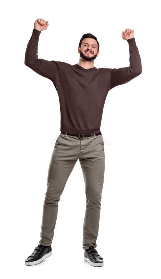 Um homem farpado feliz está no vestuário desportivo que sorri e que guarda os braços acima na vitória nos punhos apertados imagem de stock royalty free