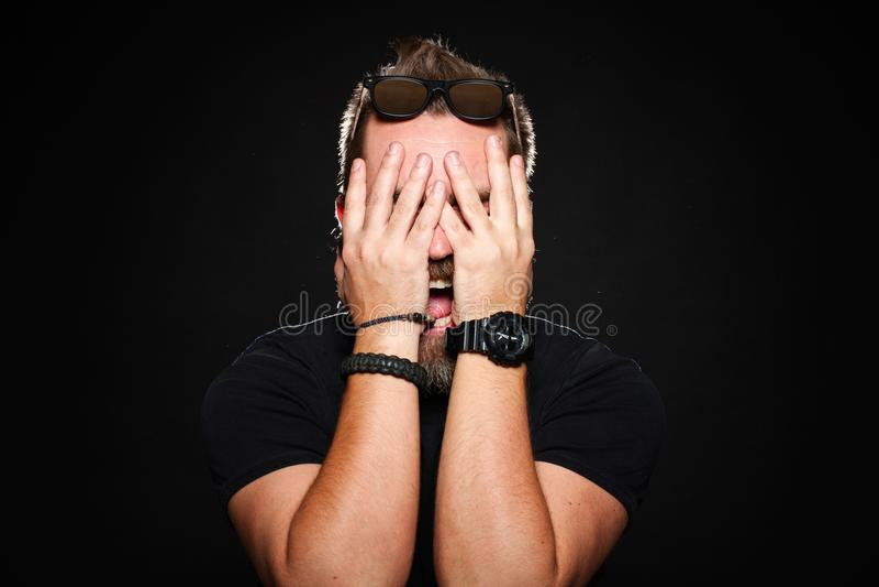 Um homem farpado guarda suas mãos atrás de sua cara e grita no estúdio em um fundo preto foto de stock
