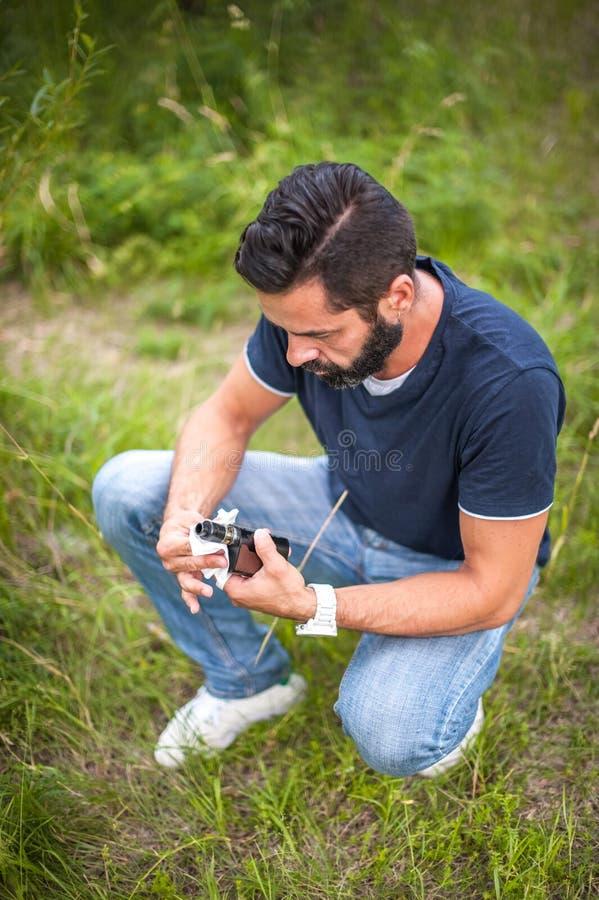 Um homem farpado na natureza prepara um cigarro eletrônico para o uso fotos de stock
