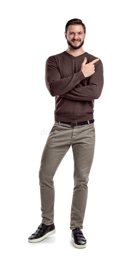 Um homem farpado na roupa ocasional mantém um sentido de sorriso e mostrando branco dobrado pé com uma das mãos cruzadas fotografia de stock