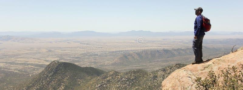 Um homem farpado que caminha nas montanhas imagem de stock