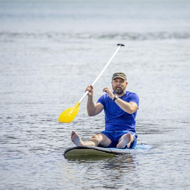 Um homem farpado que rema no oceano imagem de stock royalty free