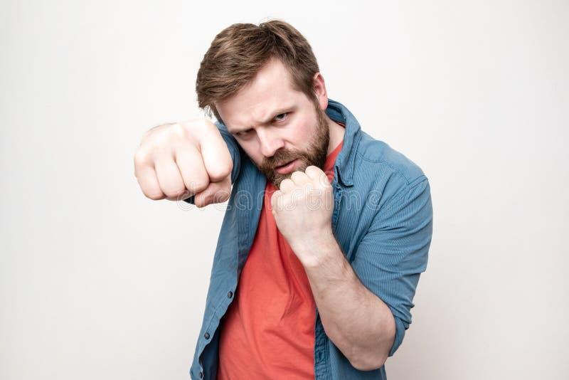 Um homem forte e confiante amontoou grandes punhos, olhou sem medo e estava prestes a se defender, num fundo branco imagens de stock royalty free