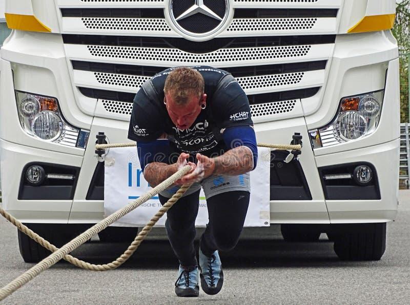 Um homem forte puxa um caminhão grande imagem de stock