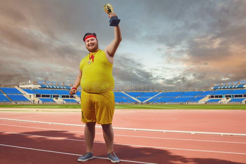 Um homem gordo com o copo de um vencedor em suas mãos no estádio imagem de stock