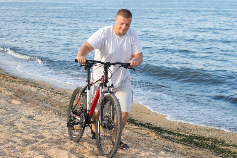 Um homem gordo conduz uma bicicleta ao longo do litoral durante o dia fotografia de stock royalty free