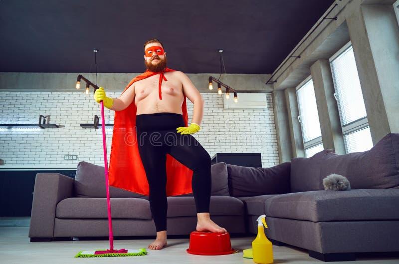 Um homem gordo, engraçado em um traje do super-herói está limpando a casa imagem de stock royalty free