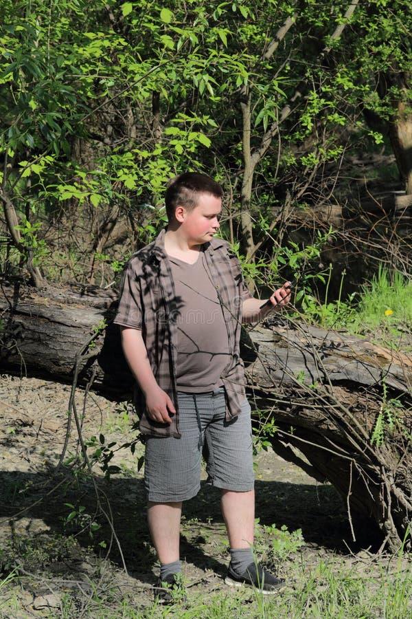Um homem gordo novo está perto de uma árvore Guarda um smartphone em sua m?o Pensativamente olhando o dispositivo imagens de stock royalty free
