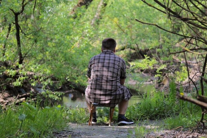 Um homem gordo novo senta-se em uma cadeira de dobramento pequena com o o seu de volta à câmera Assento nos bancos do rio que olh foto de stock royalty free
